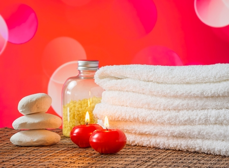 Spa massage border with towel stacked,red candles and stone on red bokeh background for valentine day