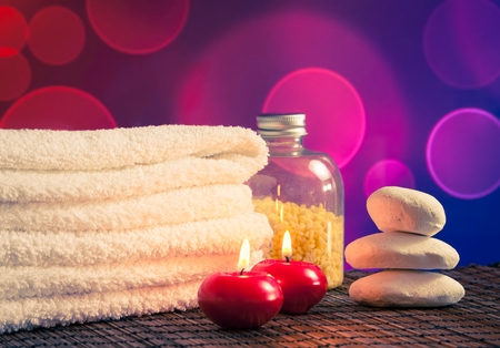 perfumed candle: Spa massage border background with towel stacked,red candles and stone on blue and violet bokeh background