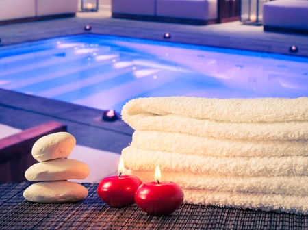 swimming candles: Spa massage border background with towel stacked,red candles and stone on swimming pool background
