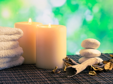 perfumed candle: Spa massage border background with towel stacked, candles and stone on green bokeh background
