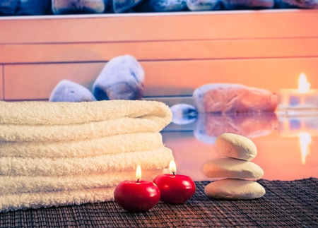 perfumed candle: Spa with towel stacked,red candles near stone on massage border background