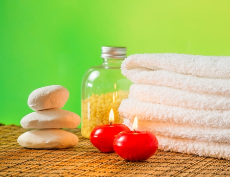 Spa massage border background with towel stacked,red candles and stone on green bokeh background photo