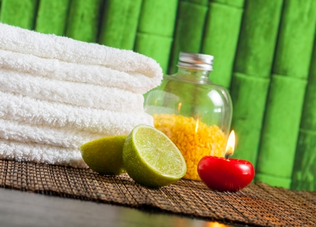 Spa massage border background with towel stacked,red candle and lime on bamboo background photo