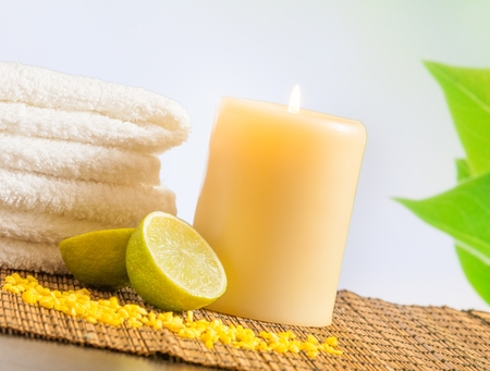 perfumed candle: Spa massage border background with towel stacked and lime with leaves in background