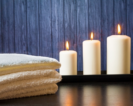 Spa massage border background with towel stacked and candles on wood background photo