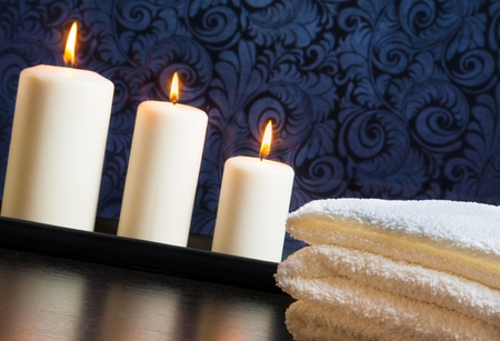 perfumed candle: Spa massage border background with towel stacked and candles on vintage background