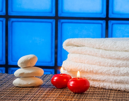 perfumed candle: Spa massage border background with towel stacked stone and red candles on blue tiles background warm atmosphere Stock Photo