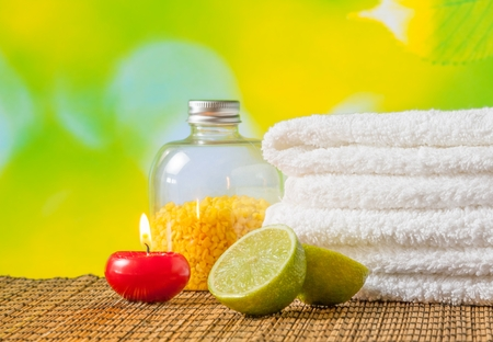 perfumed candle: Spa massage border background with towel stacked,red candle and lime on green natural background