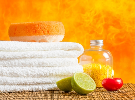 perfumed candle: Spa massage border background with towel stacked,red candle and lime on orange background Stock Photo