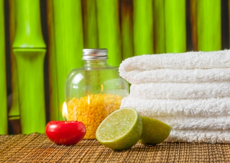 perfumed candle: Spa massage border background with towel stacked red candle and lime on bamboo background Stock Photo