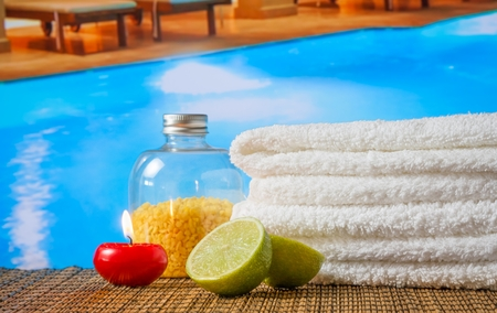 perfumed candle: Spa massage border background with towel stacked,red candle and lime on swimming pool background Stock Photo
