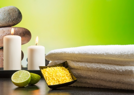 perfumed candle: Spa massage border background with towel stacked sea salt candles and lime on green background Stock Photo