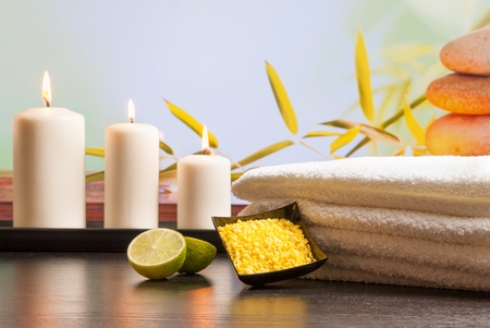 perfumed candle: Spa massage border background with towel stacked sea salt candles and lime on natural background Stock Photo