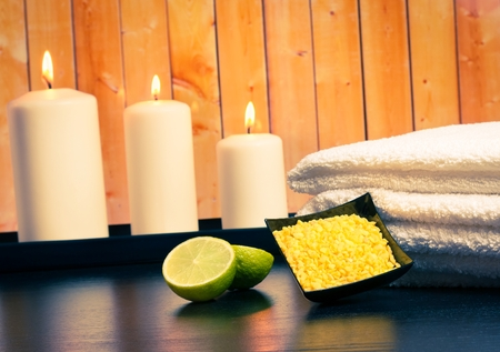 perfumed candle: Spa massage border background with towel stacked candles and sea salt and lime on wood background