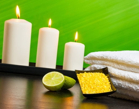 Spa massage border background with towel stacked sea salt candles and lime on green background photo