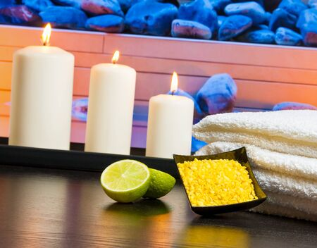Spa with towel stacked candles sea salt and lime on massage border background photo