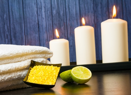 perfumed candle: Spa massage border background with towel stacked candles sea salt and lime on wood background Stock Photo
