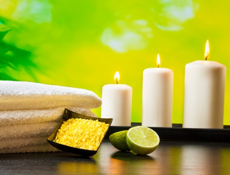 perfumed candle: Spa massage border background with towel stacked sea salt candles and lime on natural green background