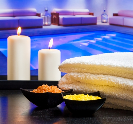perfumed candle: Spa massage border background with towel stacked candles and sea salt on swimming pool background