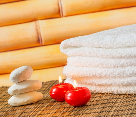 perfumed candle: Spa massage border background with towel stacked stone and red candles on bamboo background