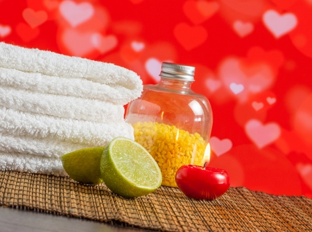 perfumed candle: Spa massage border with towel stacked red candle and lime on hearths decoration background for valentine day Stock Photo