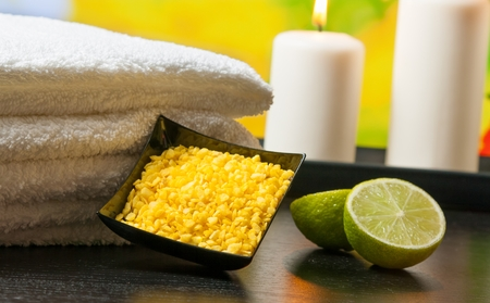 perfumed candle: Spa massage border background with towel stacked sea salt candles and lime on green natural background
