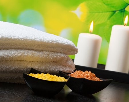 Spa massage border background with towel stacked,candles and sea salt on natural background photo