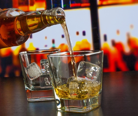 barman pouring whiskey on bar table lounge bar atmosphere Reklamní fotografie