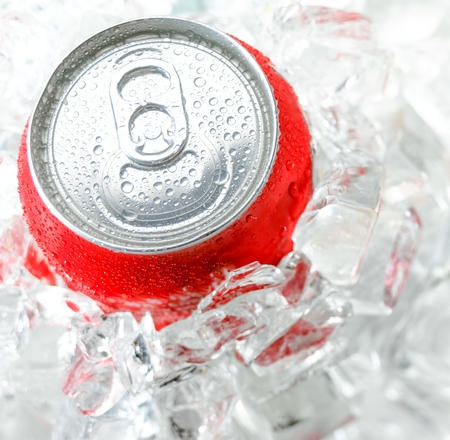 red aluminum can with water drop in the a lot of ice photo