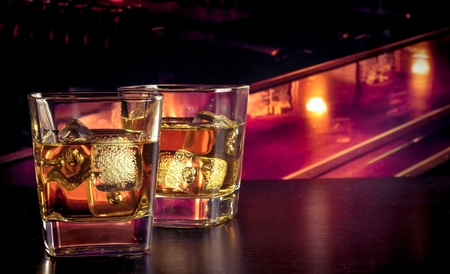 whiskey with ice on bar table lounge bar atmosphere Imagens