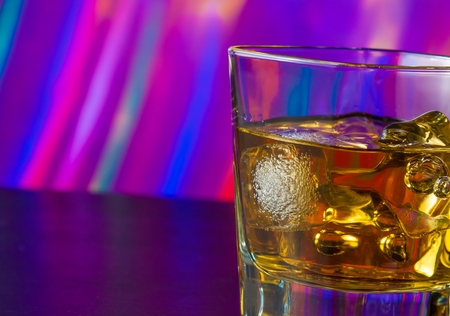 whiskey glass with ice on bar table on warm atmosphere lounge bar concept photo