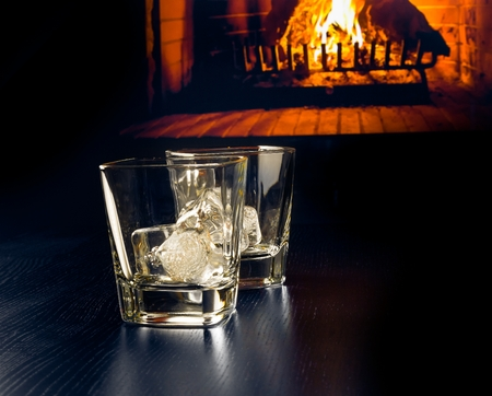 drunks: empty glasses of whiskey with ice cubes in front of the fireplace at night Stock Photo