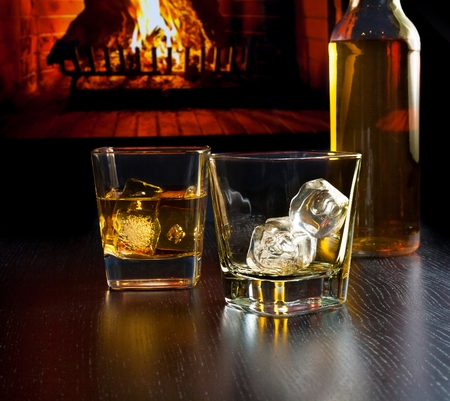 drunks: glasses of whiskey with ice cubes near whiskey bottle in front of the fireplace at night