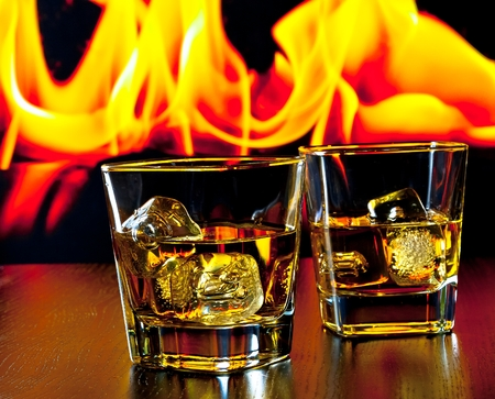 two glasses of whiskey with ice cubes in front of the flame on wood table