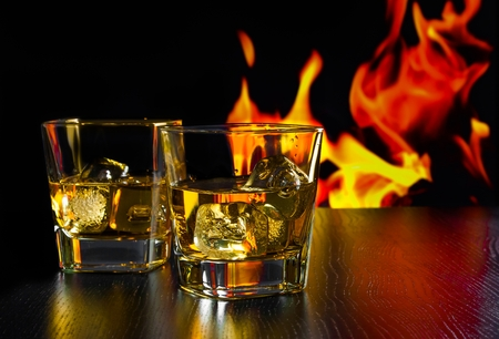 glasses of whiskey with ice cubes in front of the flame on wood table Reklamní fotografie
