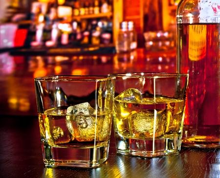 glazen whisky met ijs op de bar tafel in de buurt van whisky fles op warme sfeer loungebar begrip Stockfoto