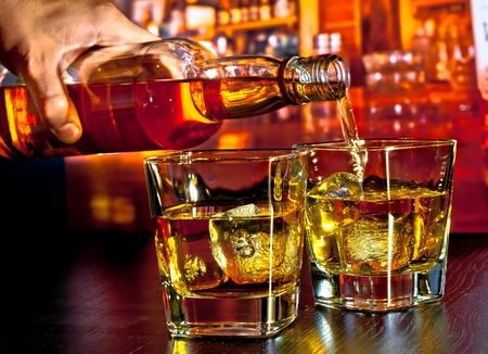 barman pouring whiskey on bar table lounge bar atmosphere Stock Photo