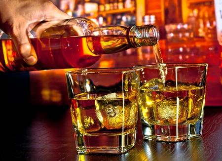 whiskey bottle: barman pouring whiskey on bar table lounge bar atmosphere Stock Photo