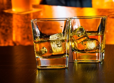 whiskey with ice on bar table on warm atmosphere lounge bar concept photo