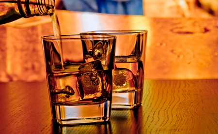 silhouette of whiskey glasses with ice on bar table on warm atmosphere lounge bar concept photo
