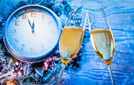 New Year or Christmas at midnight with champagne flutes with gold bubbles make cheers on blue light and clock background 스톡 콘텐츠