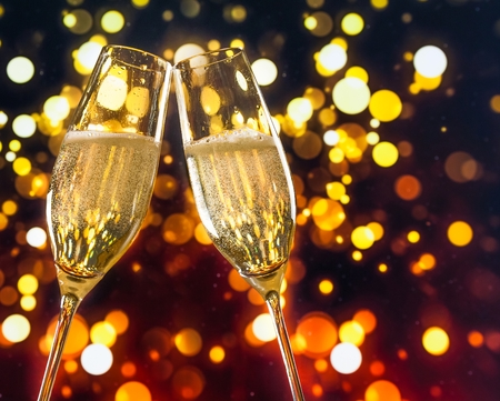 two champagne flutes with golden bubbles make cheers on colorful light bokeh background with space for text