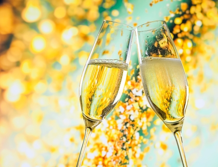 a pair of champagne flutes with golden bubbles make cheers on golden light background with space for text Foto de archivo