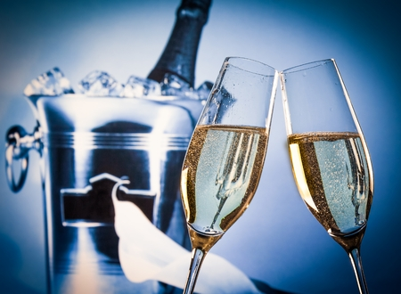 champagne flutes with golden bubbles make cheers in front of champagne bottle in bucket background photo