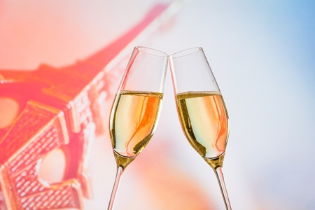 a pair of champagne flutes with golden bubbles make cheers on blur Eiffel Tower background valentine day concept photo