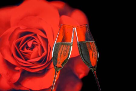 a pair of champagne flutes with golden bubbles make cheers on blur red rose background valentine day concept photo