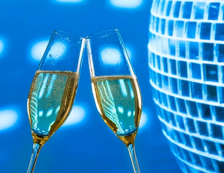 a pair of champagne flutes with golden bubbles make cheers on sparkling blue disco ball background with space for text photo