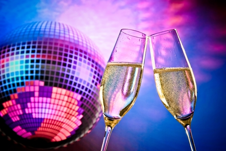 a pair of champagne flutes with golden bubbles make cheers on sparkling blue and violet disco ball background with space for text photo