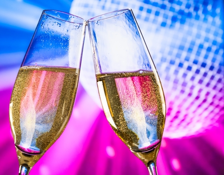 champagne flutes with golden bubbles make cheers on sparkling blue and violet disco ball background with space for text photo