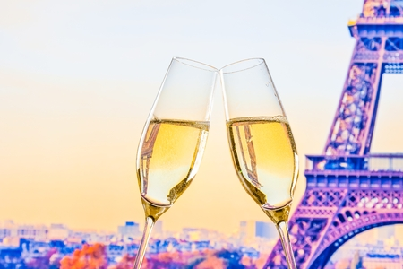 a pair of champagne flutes with golden bubbles make cheers on blur tower Eiffel background valentine day concept photo